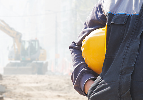 construction worker holding a yellow hard hat